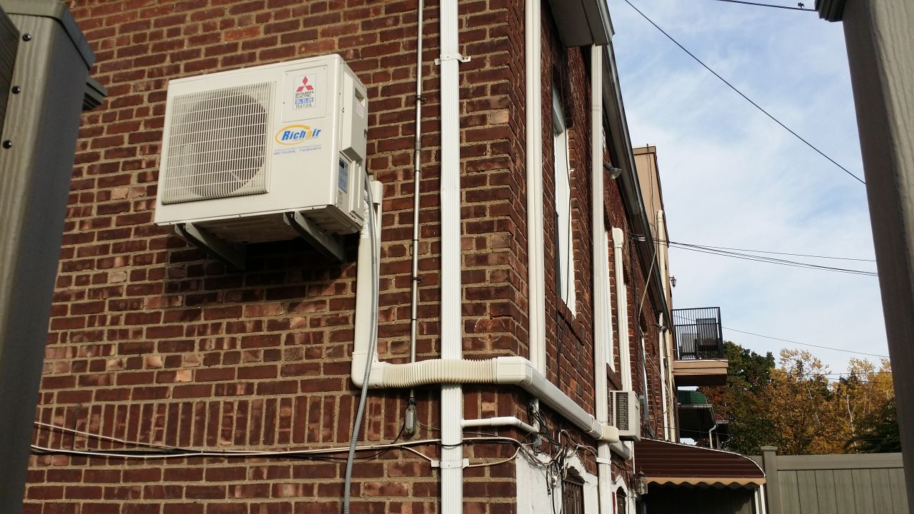 Mini split outdoor unit installed on brick wall in Astoria, NY